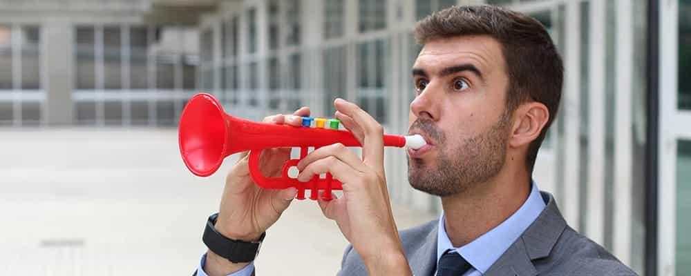 Hombre tocando una trompeta de plástico