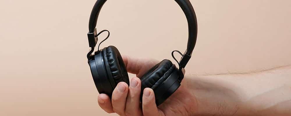 Auriculares inalámbricos en la mano del hombre
